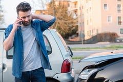 Человек вызывая обслуживание обочины после автокатастрофы стоковые изображения