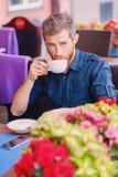 Человек выпивает кофе в кафе на улице Стоковое Изображение RF