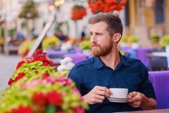 Человек выпивает кофе в кафе на улице Стоковые Изображения RF