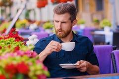 Человек выпивает кофе в кафе на улице Стоковое Фото