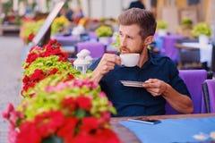 Человек выпивает кофе в кафе на улице Стоковые Изображения
