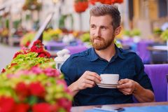 Человек выпивает кофе в кафе на улице Стоковые Фото