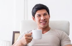Человек выпивает питье чая кофе окнами утра Стоковое Изображение