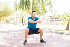 Человек выполняя сидения на корточках перед Jogging на тропе в парке стоковые фото
