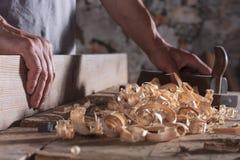 Человек выскабливая завитые деревянные утили с рукой строгает инструмент стоковая фотография