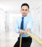 Человек вытягивая веревочку стоковое фото