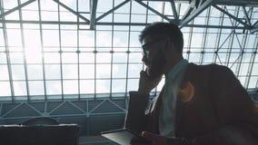 Человек в авиапорте говорит на телефоне и держит таблетку в его руках акции видеоматериалы