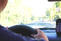 Человек в автомобиле и держать черный мобильный телефон при навигация gps карты, тонизированная на заходе солнца стоковые изображения rf