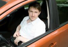Человек в автомобиле с netbook стоковое изображение