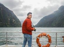 Человек в апельсине вниз с куртки с камерой на круизе пассажира для принимать фото на Milford Sound в Новой Зеландии стоковое изображение rf