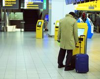 Человек в аэропорте с чемоданом около терминала для покупки билета стоковые изображения rf