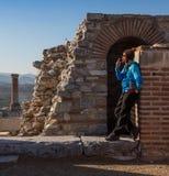 Человек в бейсбольной кепке NYC сидит под дугой строба Augustus в Ephesus был построен для того чтобы удостоить императора стоковые фото