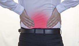 Человек в белой рубашке держит дальше к задней части, боли в спине, красному цвету назад, белый бизнесмен предпосылки стоковые фото