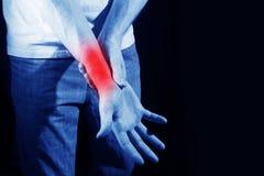 Человек в белой футболке держит дальше к плечу, руке, запястью руки, предплечью, ушибу спорт, перелому кости, испытывая боль, на  Стоковая Фотография RF