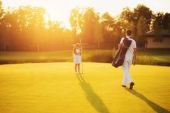 Человек в белом костюме и сумке гольф-клуба идет к девушке которая стоит рядом с отверстием в заходе солнца Стоковая Фотография