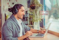 Человек в бортовом профиле усмехаясь имеющ онлайн разговор, видео-чат стоковая фотография rf