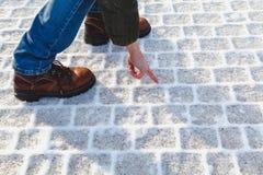 Человек в ботинках касается налет инее на плитке тротуара Стоковое Фото