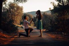 Человек в влюбленности предлагая удивленную, сотрясенную женщину пожениться он на заходе солнца Концепция предложения, захвата и  Стоковые Фотографии RF
