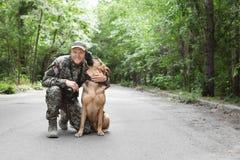 Человек в военной форме с собакой немецкой овчарки Стоковое Изображение RF