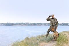 Человек в военной форме с собакой немецкой овчарки Стоковая Фотография