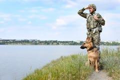Человек в военной форме с собакой немецкой овчарки outdoors стоковое фото rf