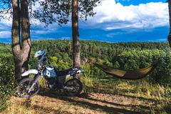 Человек в гамаке на горе соснового леса, на открытом воздухе путешественник ослабляет, enduro с мотоцикла дороги стоковое фото rf