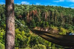 Человек в гамаке на горе соснового леса, на открытом воздухе путешественник ослабляет, enduro с мотоцикла дороги стоковая фотография rf