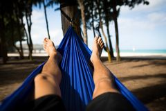 Человек в гамаке смотрит на пляж со счастливыми ногами стоковые фотографии rf