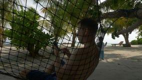 Человек в гамаке с мобильным телефоном на пляже, на заднем плане девушка играя с пузырями мыла сток-видео