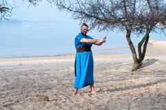 Человек в голубом кимоно с поясом, плюшкой и ручками стоя и держа шпага стоковое изображение
