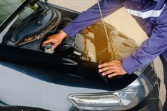 Человек в двигателе автомобиля голубой безопасности равномерном проверяя Стоковые Фотографии RF