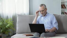 Человек в его 50s работая на компьтер-книжке дома, профессия и работать, устройство Стоковые Фото