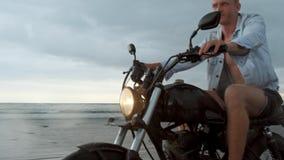Человек в ехать мотоцикле на пляже винтажный мотоцикл на заходе солнца пляжа на Бали Молодой мужчина хипстера наслаждаясь свободо сток-видео