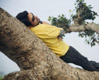 Человек в желтой рубашке лежа на частях дерева стоковые фото