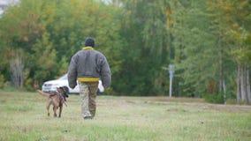 Человек в защитной и натренированной собаке идет далеко от камеры сток-видео