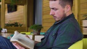Человек в зеленой рубашке читает книгу в кафе видеоматериал