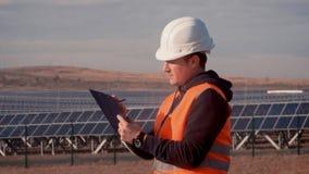 Человек в инженере шлема на предпосылке электрической станции солнечной энергии держа цифровой планшет акции видеоматериалы