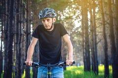 Человек в катании шлема на горном велосипеде в древесинах Велосипедист в движении Концепция активного и здорового образа жизни стоковые изображения rf
