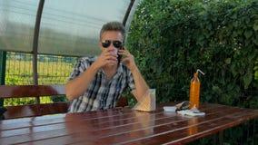 Человек в кафе говоря по телефону акции видеоматериалы