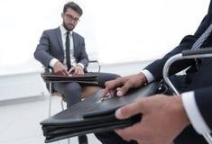 Человек в классическом костюме держит коричневый конец-вверх портфеля Стоковое фото RF
