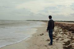 Человек в классическом положении платья на песчаном пляже стоковые фотографии rf