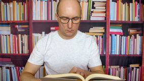 Человек в книге чтения стекел на таблице в домашнем офисе на предпосылке книжных полков видеоматериал