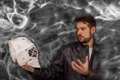 Человек в кожаной куртке держа шлем голкипера в его руке стоковые изображения rf