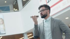 Человек в костюме держит smartphone, диктует текст сообщения сток-видео