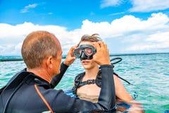 Человек в костюме для нырять подготавливает мальчика нырнуть стоковые фотографии rf