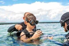 Человек в костюме для нырять подготавливает мальчика нырнуть стоковая фотография