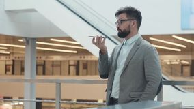 Человек в костюме записывая сообщение голоса на smartphone видеоматериал