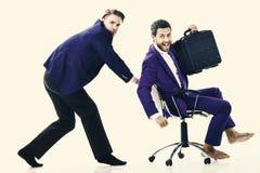 Человек в костюме или бизнесмен нажимая стул офиса с коллегой с портфелем дальше, изолированный на белой предпосылке Стоковое фото RF