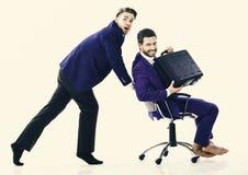 Человек в костюме или бизнесмен нажимая стул офиса с коллегой с портфелем дальше, изолированный на белой предпосылке Стоковая Фотография RF