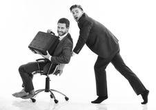 Человек в костюме или бизнесмен нажимая стул офиса с коллегой с портфелем дальше, изолированный на белой предпосылке Стоковые Фотографии RF